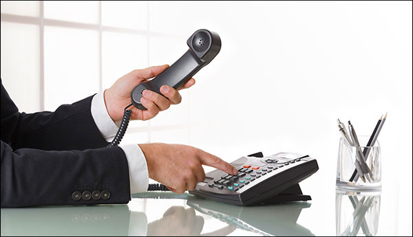 business man dialing VoIP phone
